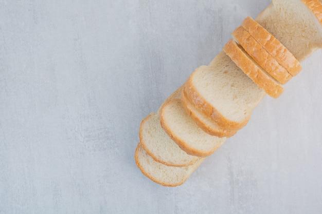 Tranches de pains blancs frais sur fond de marbre.