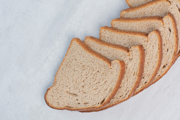 Tranches de pains bruns frais sur fond de marbre.