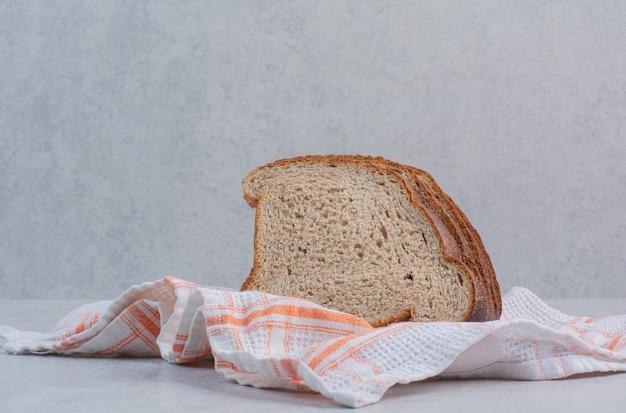 Tranches de pains bruns frais sur nappe.