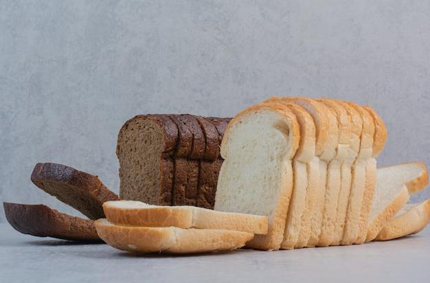 Tranches de pains frais blancs et bruns sur fond de marbre.