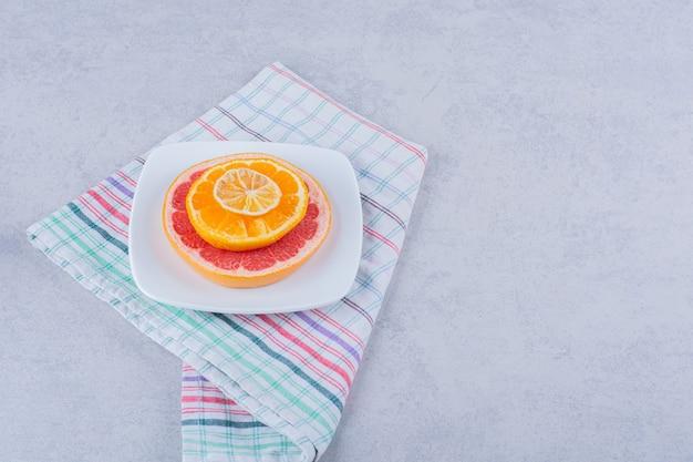 Tranches de pamplemousse frais, orange et citron sur plaque blanche.