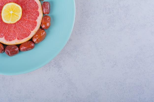 Tranches de pamplemousse mûr, de citron et de mûres d'argent sur plaque bleue.