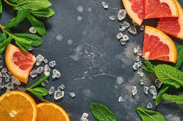 Tranches de pamplemousse et d'orange, menthe, sucre de canne, glace, tubes à cocktail
