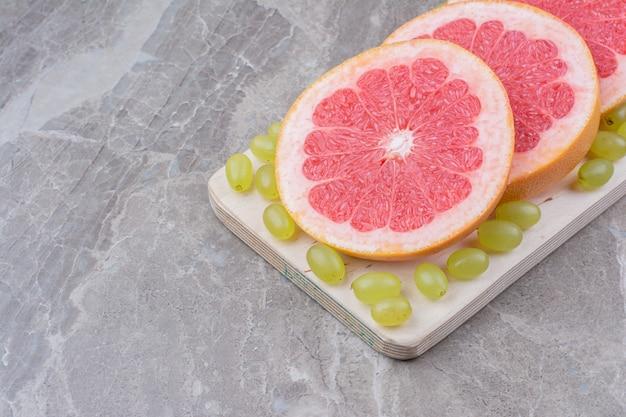 Tranches de pamplemousse et raisins sur planche de bois.