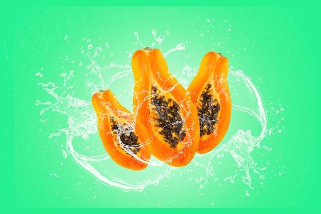 Tranches de papaye avec éclaboussures d'eau isolées sur fond noir vert.