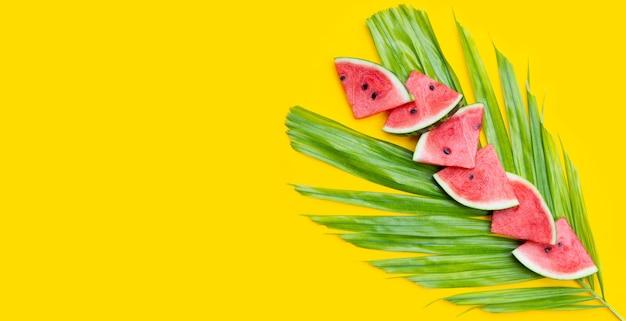 Tranches de pastèque sur des feuilles de palmiers tropicaux sur une surface jaune