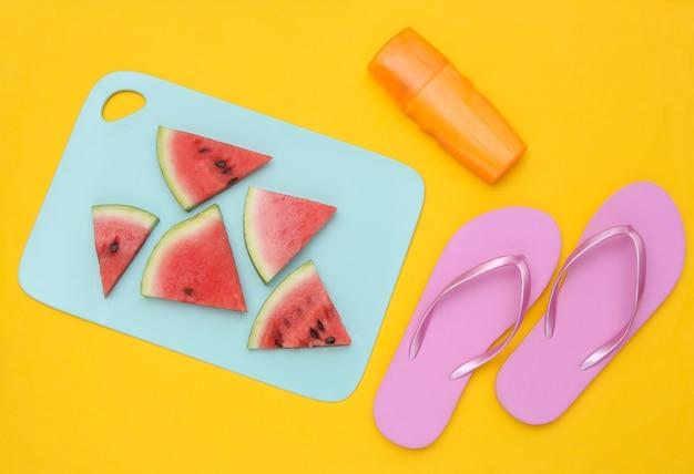 Tranches de pastèque mûre sur une planche bleue, accessoires de plage. fond jaune. heure d'été. vue de dessus. mise à plat