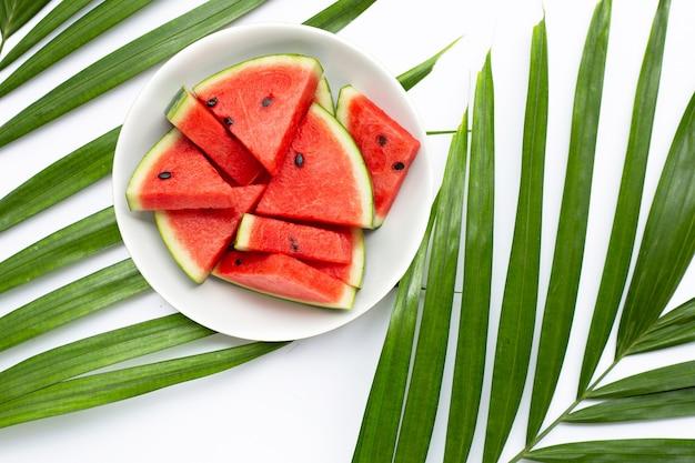 Tranches de pastèque en plaque blanche sur des feuilles de palmiers tropicaux sur blanc