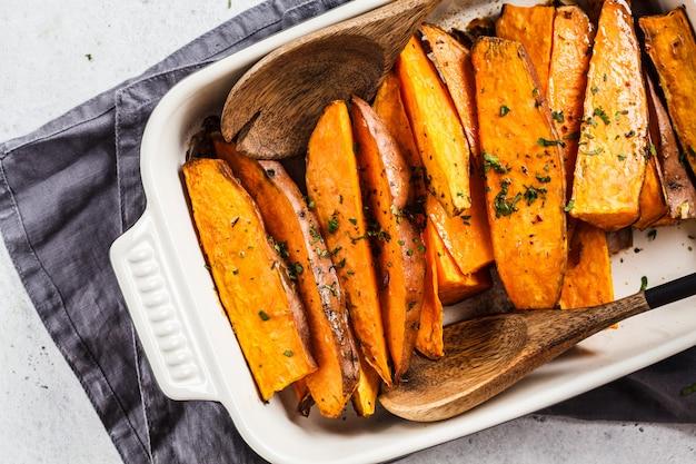 Tranches de patates douces cuites au four avec des épices dans un plat à four. concept de nourriture végétalienne saine.