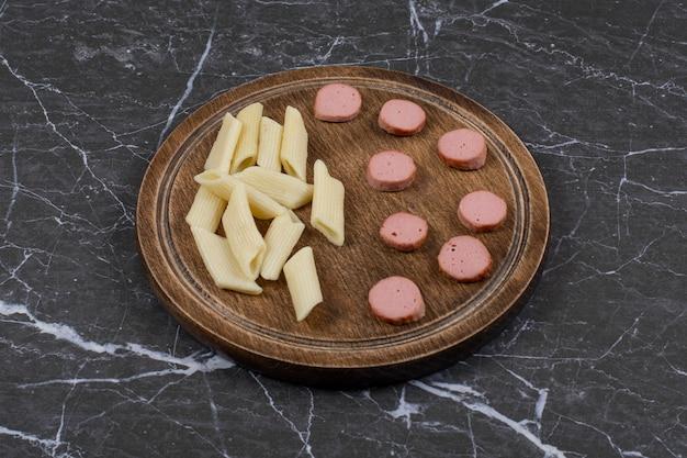 Tranches de pâtes et de saucisses bouillies sur bois.