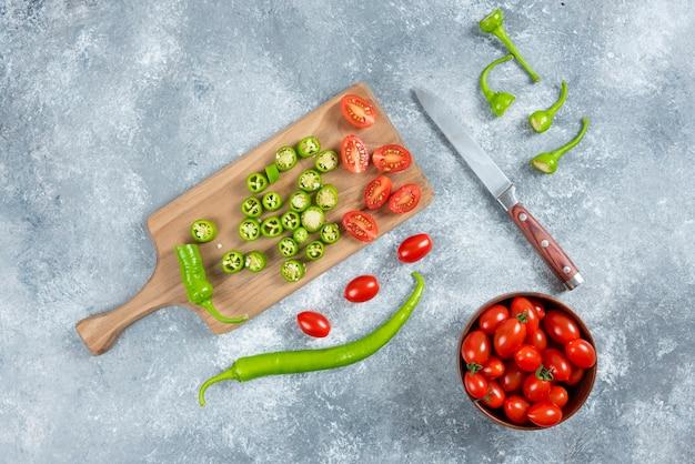 Tranches de piments jalapeno et tomates sur planche de bois.