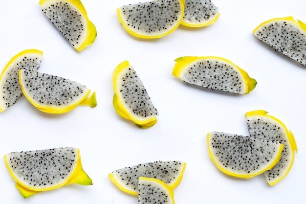 Tranches de pitahaya jaune ou de fruit du dragon sur fond blanc.