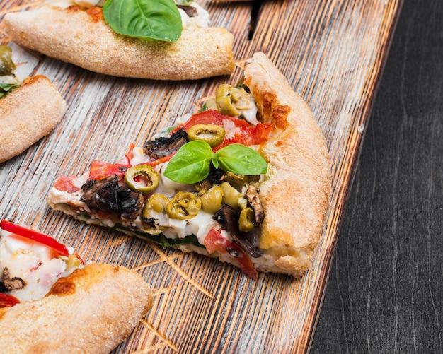 Tranches de pizza à angle élevé sur une planche à découper