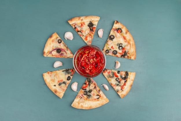 Tranches de pizza et bol de poivrons rouges marinés sur table bleue.