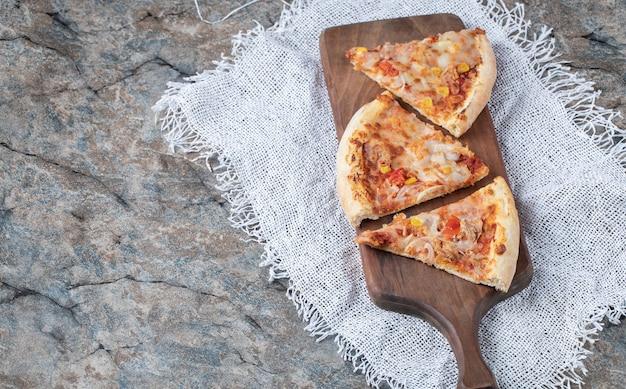 Tranches de pizza avec du fromage fondu sur le dessus sur une planche en bois sur un morceau de toile de jute blanche