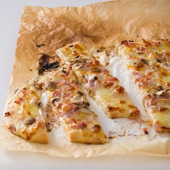 Tranches de pizza sur papier parchemin sur fond blanc
