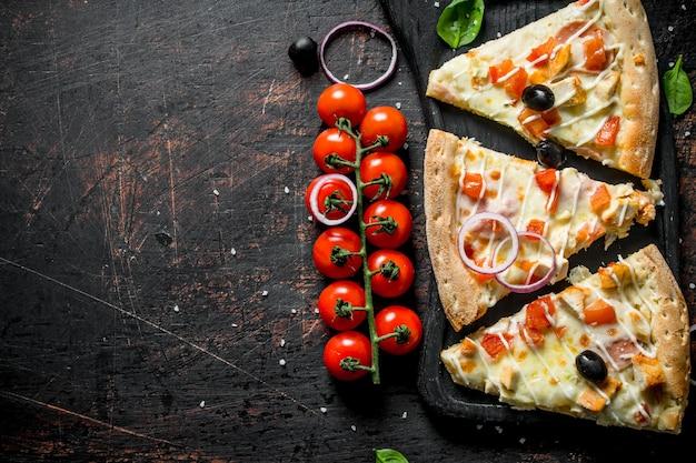 Tranches de pizza parfumées sur une planche à découper sur une table rustique sombre.