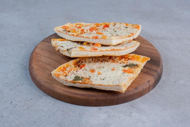 Tranches de pizza sur une planche de bois sur fond de marbre.