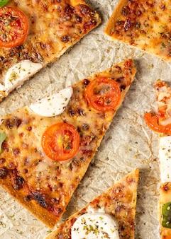 Tranches de pizza à plat sur du papier sulfurisé