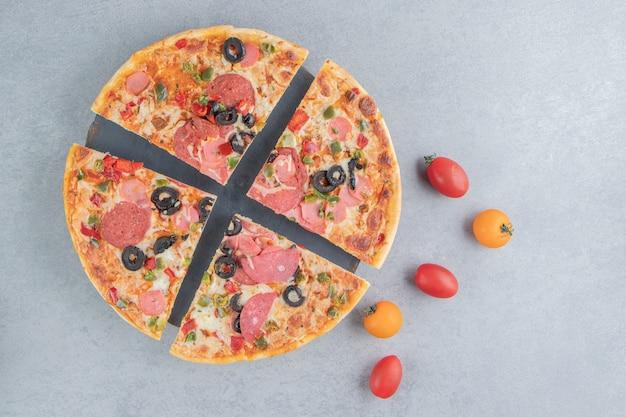 Tranches de pizza sur un plateau à côté de petites tomates sur marbre