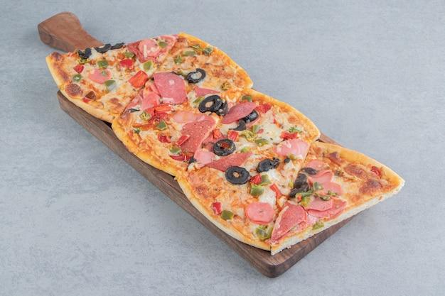 Tranches de pizza regroupées sur un petit plateau sur marbre
