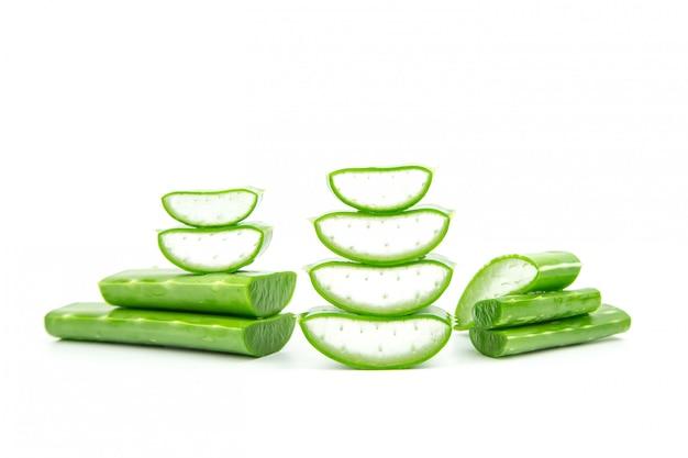Tranches de plante fraîche d'aloe vera empilées et tige d'aloe vera ou de feuilles avec de l'eau goutte à goutte isoler sur fond blanc.