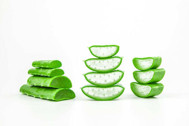 Tranches de plantes fraîches d'aloe vera empilées et tige d'aloe vera ou de feuilles avec de l'eau goutte isoler sur blanc