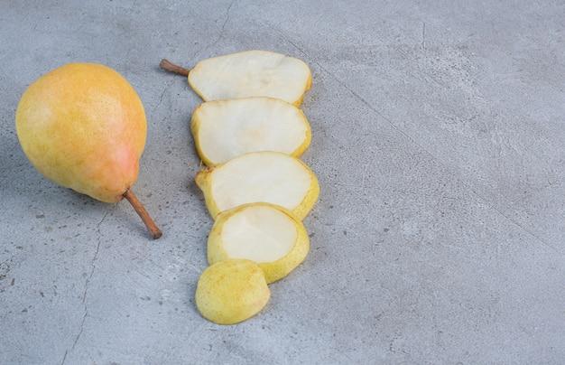 Tranches de poire alignées à côté d'une poire entière sur fond de marbre.