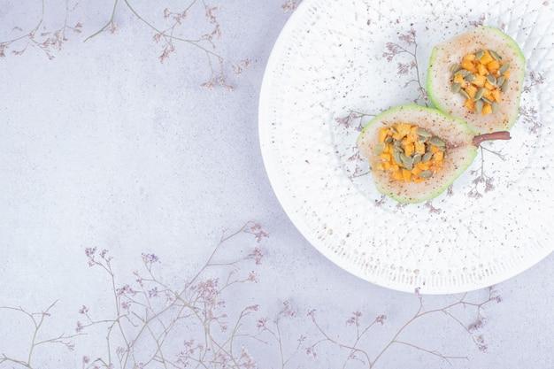 Tranches de poire cuites aux herbes et épices dans une assiette blanche.