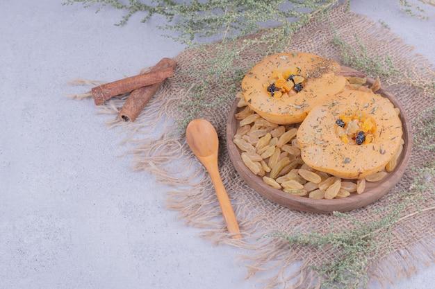 Tranches de poire dans une assiette en bois avec raisins secs et cannelle