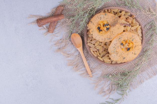 Tranches de poire frites aux épices et raisins secs dans un plateau en bois.
