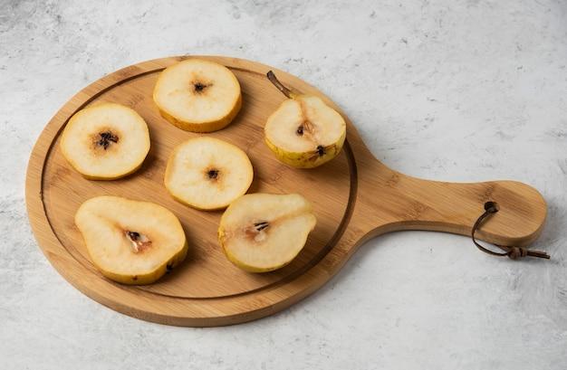 Tranches de poire sur un plateau en bois.