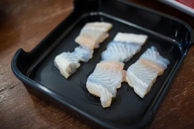 Des tranches de poisson frais dolly cru ont été servies pour le restaurant sukiyaki et shabu ou yakiniku qu'il a mis sur une assiette noire.