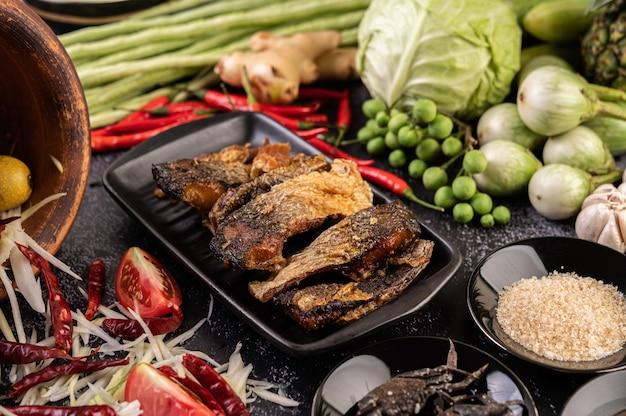 Tranches de poisson frit dans une assiette noire.