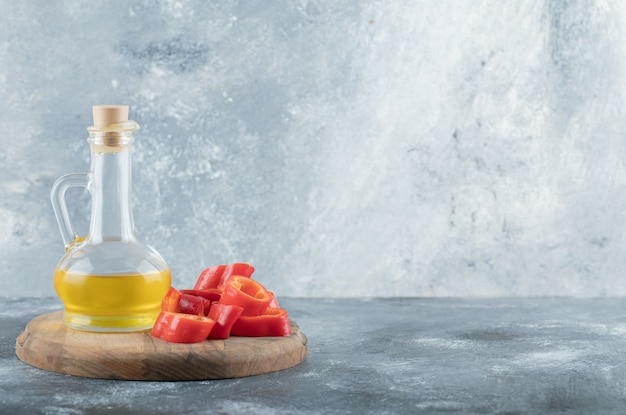 Tranches de poivron rouge doux avec une bouteille d'huile en verre sur une planche de bois.