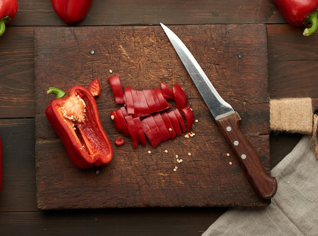 Tranches de poivron rouge sur une planche de bois