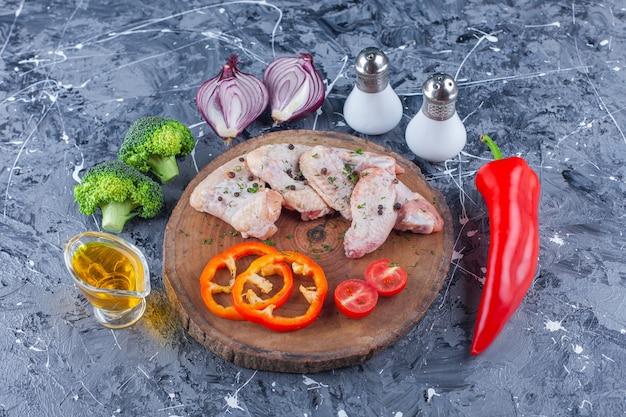 Tranches de poivron, tomates et aile sur une planche à côté de l'oignon, sel et poivre sur la surface bleue