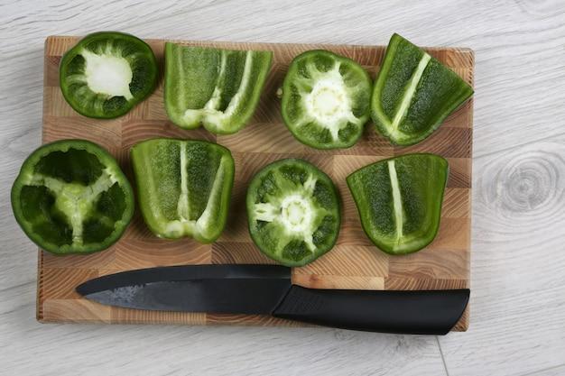 Tranches de poivrons doux avec un couteau en céramique sur une planche de bois
