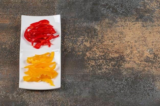 Tranches de poivrons rouges et jaunes sur plaque blanche.