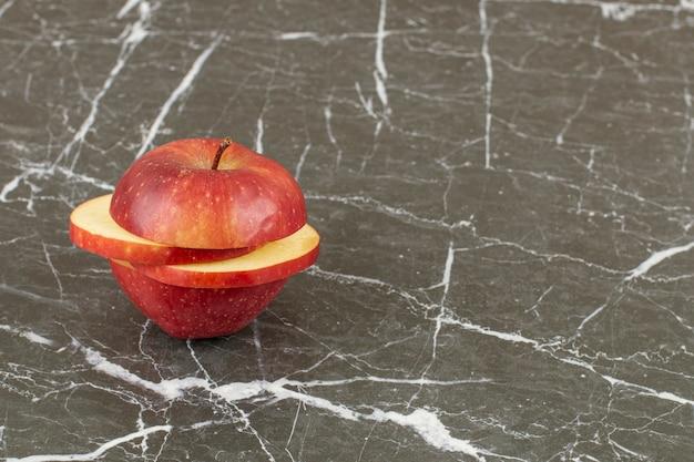 Tranches de pomme biologique rouge sur fond gris.