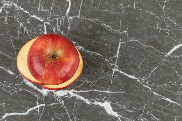 Tranches de pomme rouge fraîche sur fond gris.