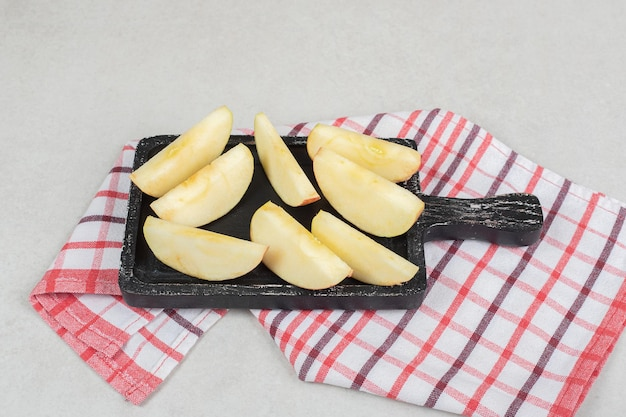 Tranches de pomme rouge fraîche sur tableau noir