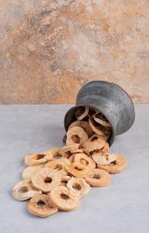 Tranches de pomme séchées dans un pot métallique.