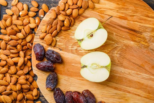 Tranches de pomme verte aux dattes et aux amandes sur fond de planche à découper en bois