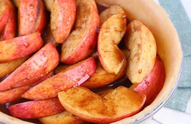 Tranches de pommes fraîches mélangées avec de la cassonade et des épices placées dans une assiette à tarte tapissée de pâte
