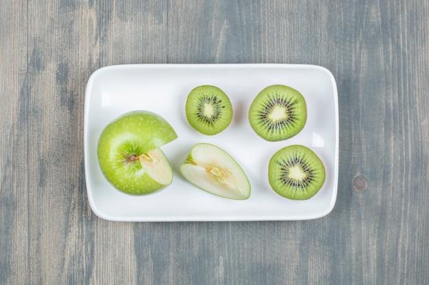 Tranches de pommes avec kiwi frais sur une table en bois