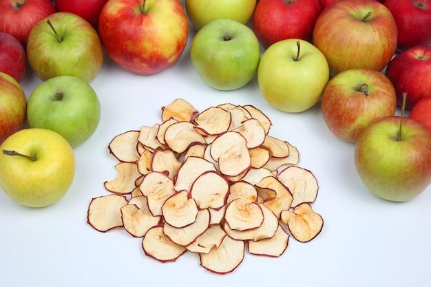 Tranches de pommes séchées entourées de pommes fraîches sur un espace blanc