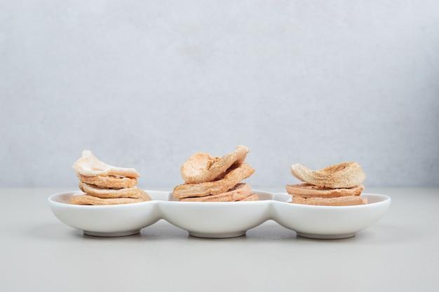 Tranches de pommes séchées sur plaque blanche