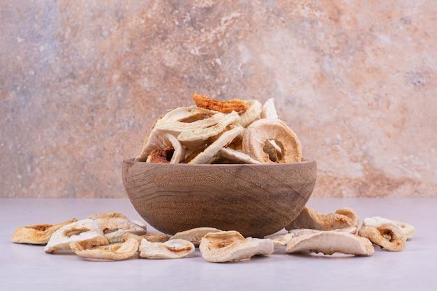 Tranches de pommes sèches dans un bol en bois rustique