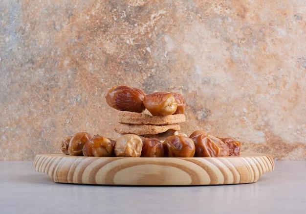 Tranches de pommes sèches et dates sur fond de béton.